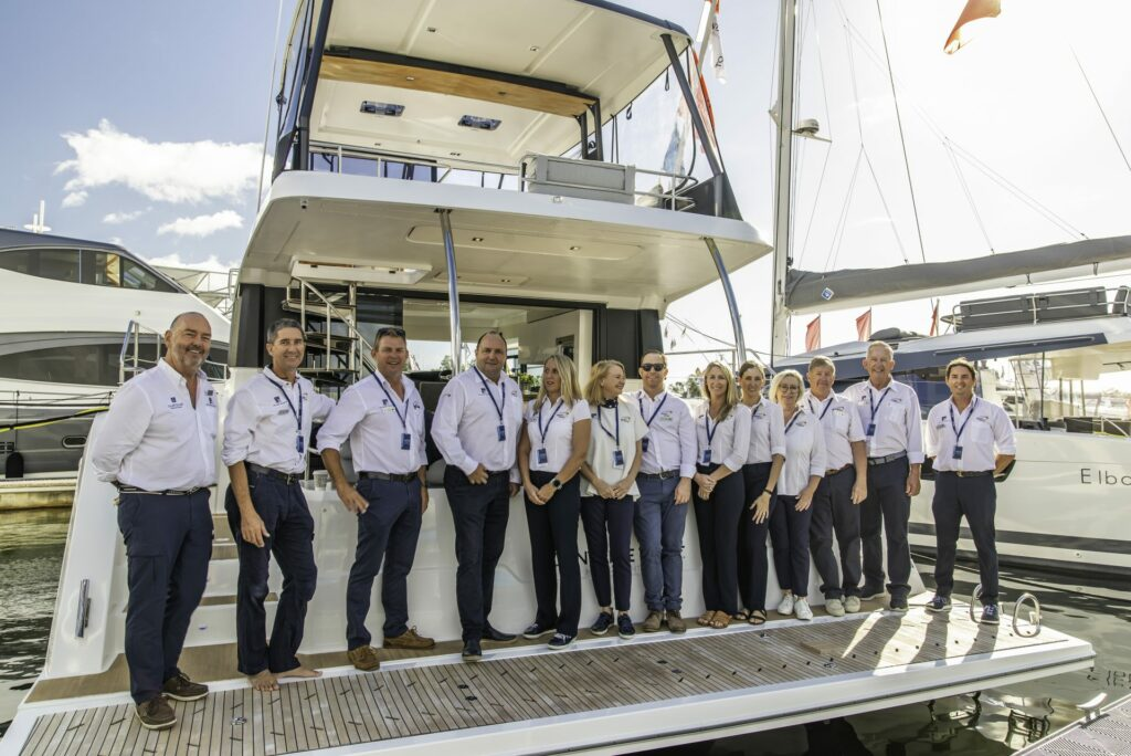 Multihull Solutions team pictured aboard the aft deck of a vessel displayed at Sanctuary Cove International Boat Show