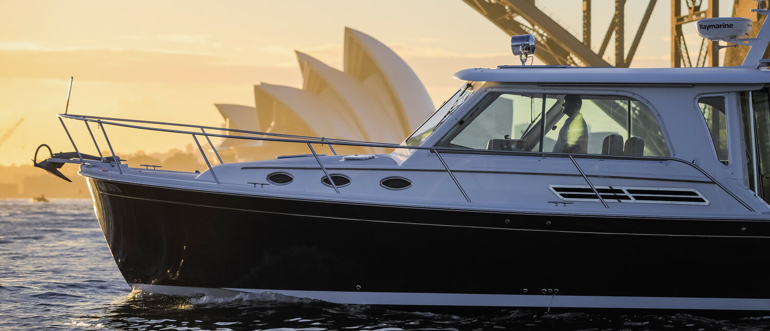 Back Cove Yacht cruising in front of the Ooera House and Harbour Bridge