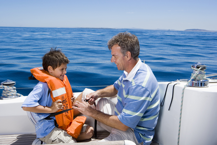 father and son wearing life jackets onboard motor yacht