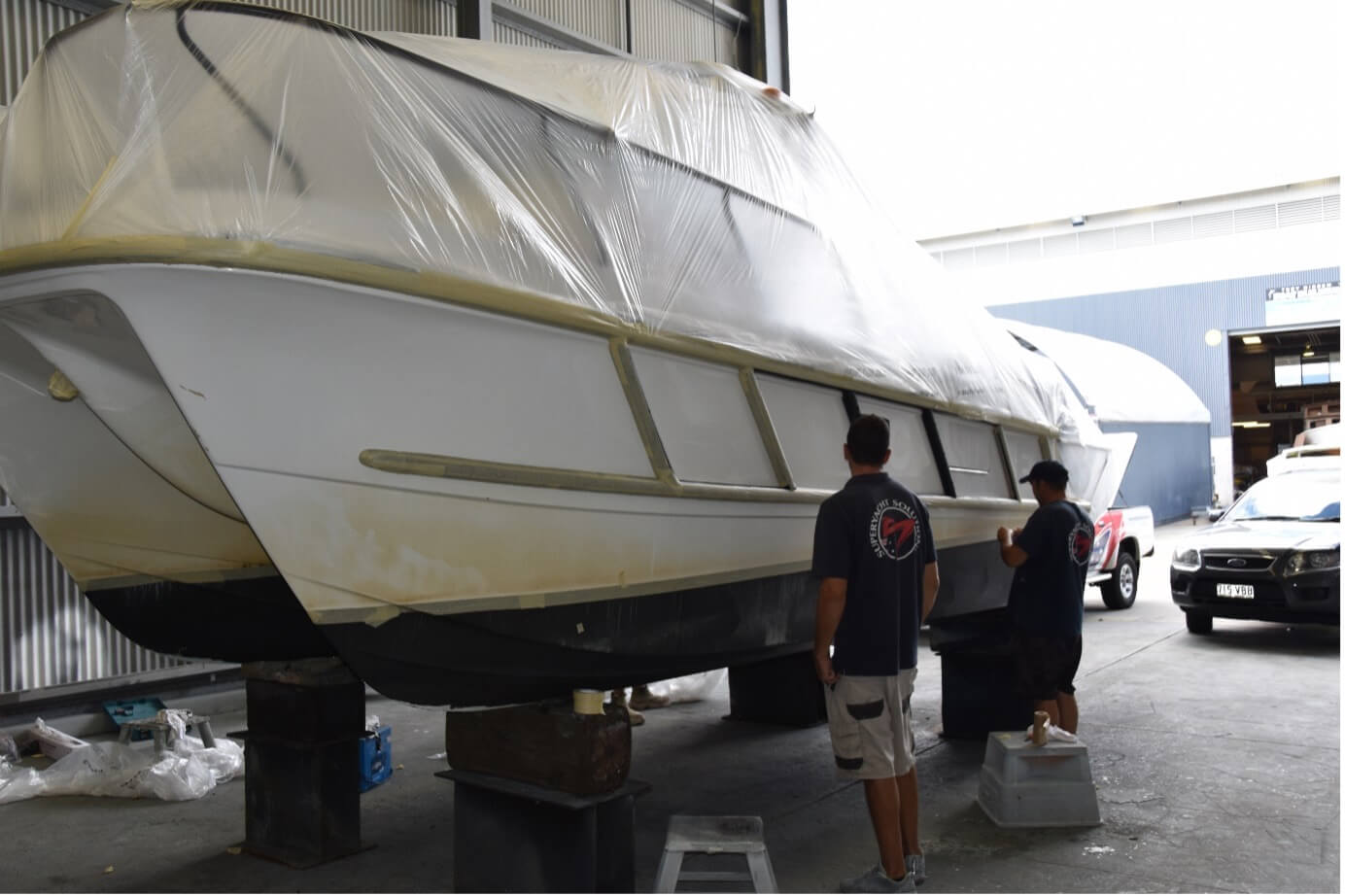 volunteer boat being painted at GCCM by two workers