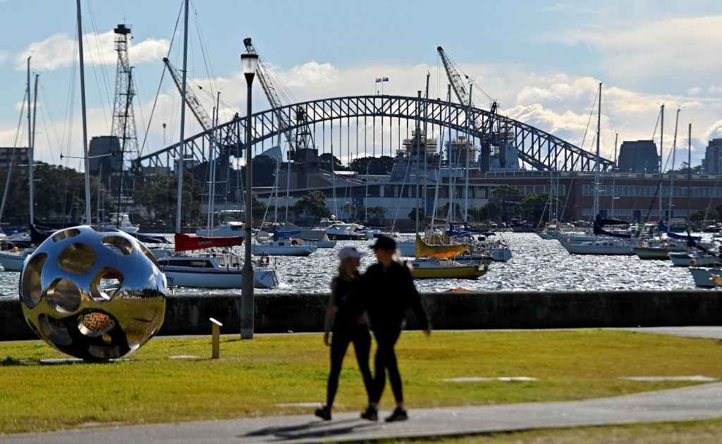people walking infront of harbour bridge with boats in background