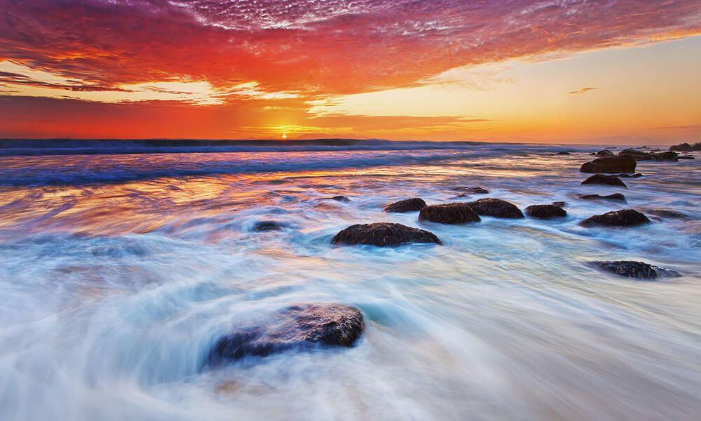 sunset and waves at a rocky beach