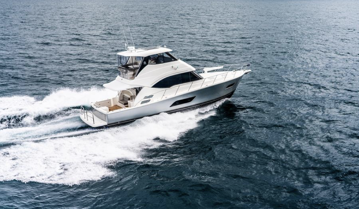 Riviera 54 Enclosed Flybridge pictured cruising from the side