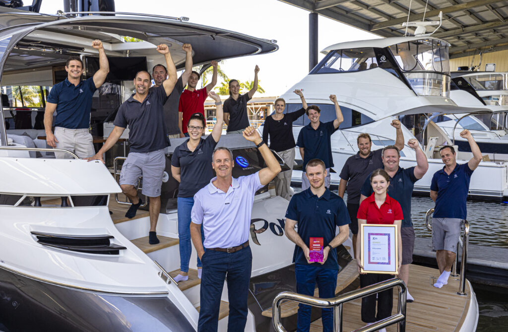 Riviera team celebrating their Export award on the aft of a Riviera vessel