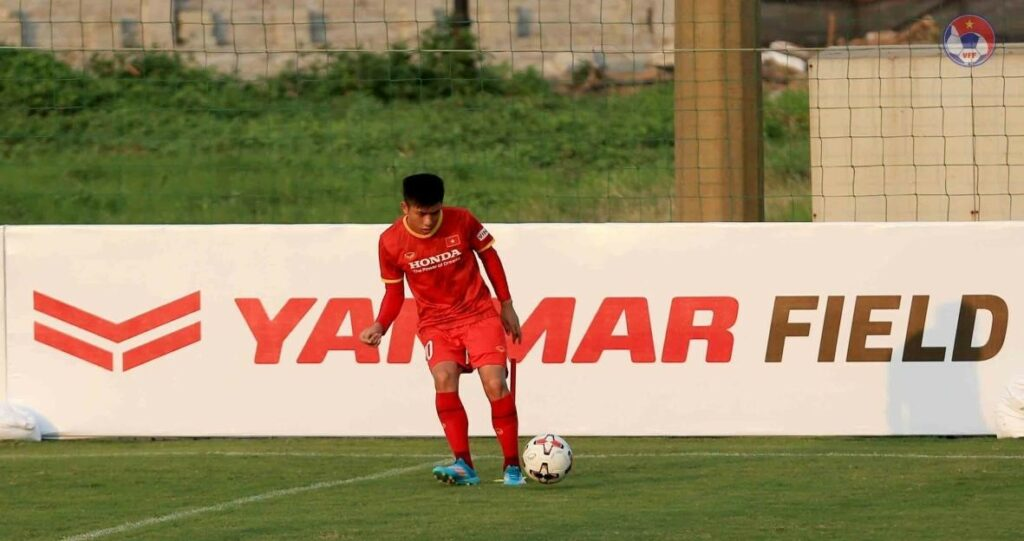 YANMAR field sponsorship sign with soccer player in foreground